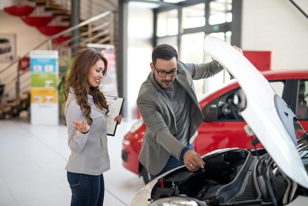 Autohandelaar die voertuig aan de koper voorstelt