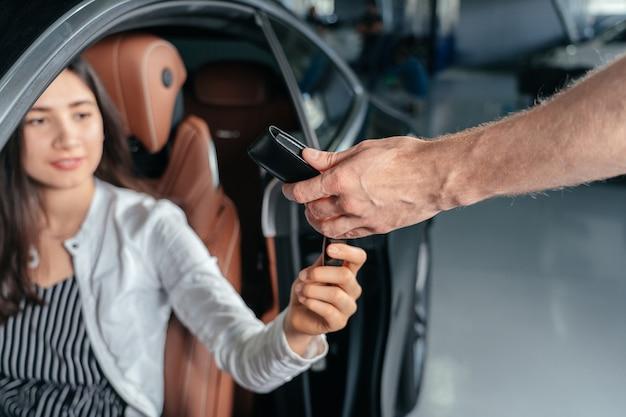 Autohandelaar geeft sleutel voor een nieuwe auto aan jonge vrouw
