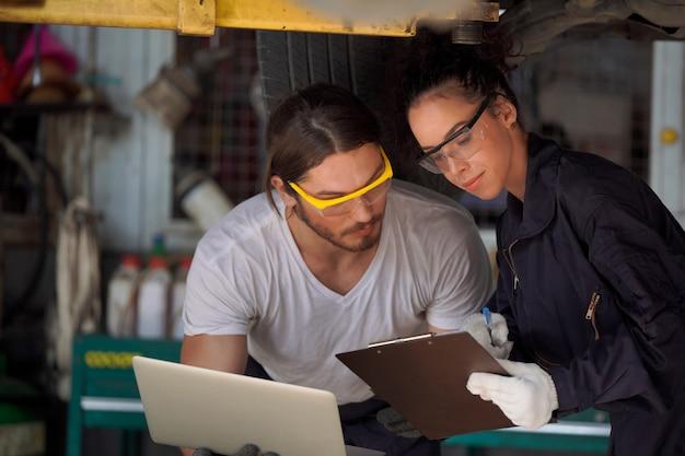 Autokeuring met laptop door bekwame technici, technologieconcept