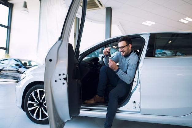 Autokoper die sleutels van nieuw voertuig houden en glimlachen