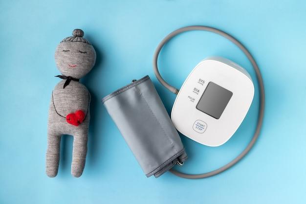 Automatische bloeddrukmeter en leuk stuk speelgoed met hart op blauwe muur. gezondheidszorg concept