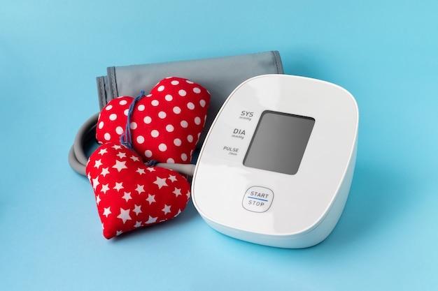 Automatische bloeddrukmeter en twee harten op blauwe muur. medische elektronische tonometer