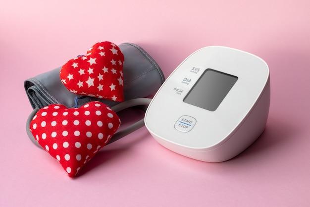 Automatische bloeddrukmeter en twee rode harten op roze muur. medische elektronische tonometer