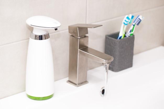 Automatische dispenser van vloeibare zeep in de badkamer