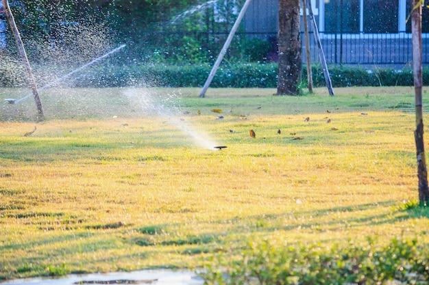 Automatische gazonsproeiers die over groen gras in de tuin water geven