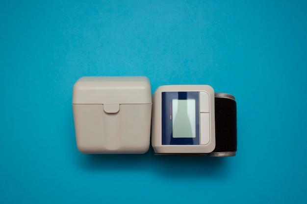 Automatische pols digitale bloeddrukmeter op blauwe achtergrond.