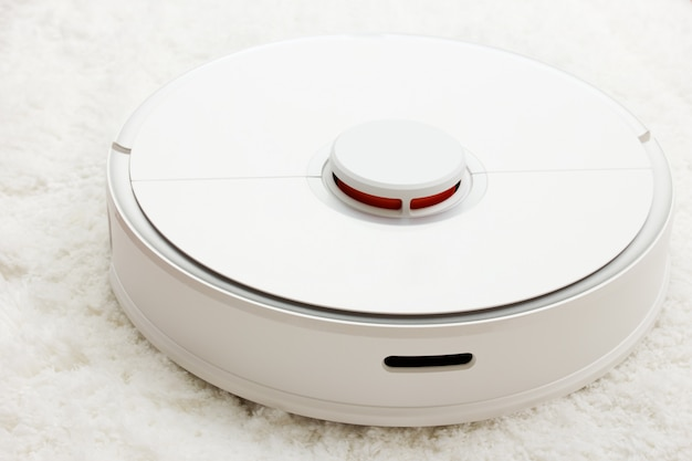 Automatisering schoonmaken. witte robotstofzuiger verzamelt stof, haar op het tapijt