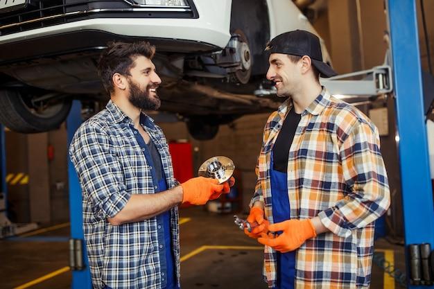 Automechanica met opgeheven auto op de achtergrond in het tankstation praten over autodetail