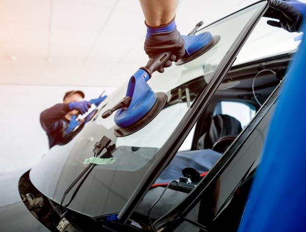 Automobiele speciale arbeiders die voorruit of voorruit van een auto in autobenzinestationgarage vervangen.