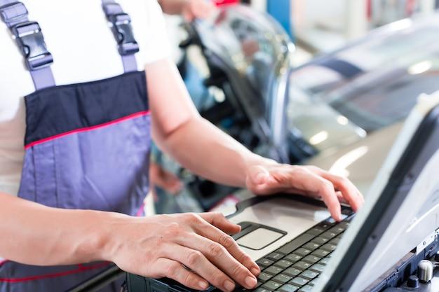 Automonteur auto-motor met diagnosetool in zijn werkplaats controleren Premium Foto