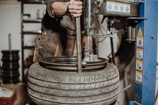 Automonteur band verwijderen van velg met apparatuur voor het verwijderen van banden, pneumatische moersleutel schroeft het wiel los