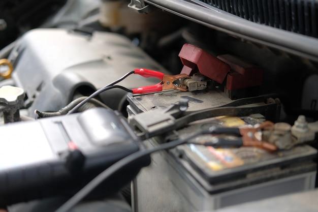 Automonteur check auto batterij spanning door voltmeter multimeter