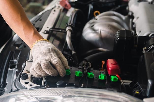 Automonteur controleer de accu van de auto gedestilleerd waterpeil