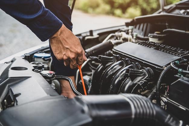 Automonteur controleert het oliepeil van het voertuig voor het verversen van motorolie van een auto