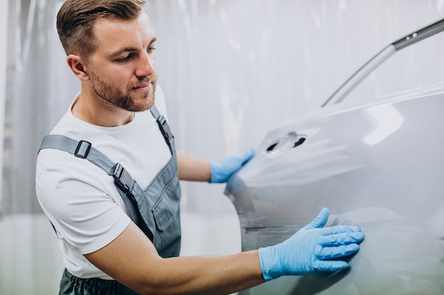 Automonteur die de autovleugel voorbereidt voordat deze wordt geverfd