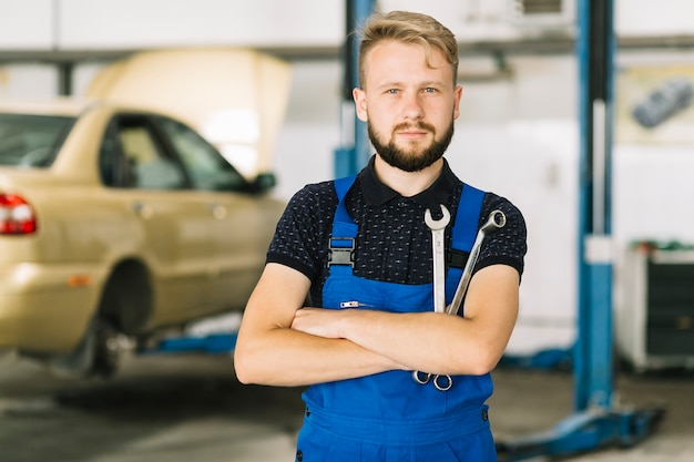 Automonteur die handen met moersleutels kruist