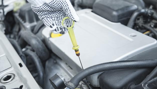 Automonteur die het oliepeil van de motor van een auto controleert.