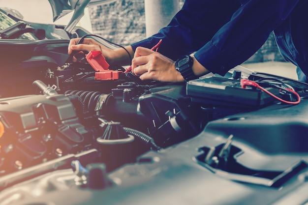 Automonteur die het voltage van de autobatterij controleert
