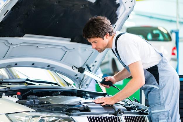 Automonteur die in autoservice-werkplaats werkt