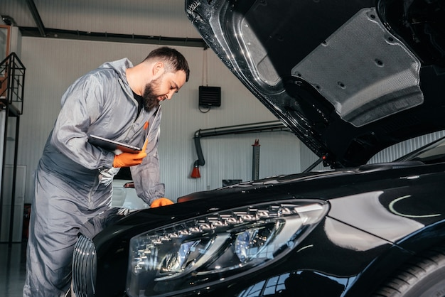 Automonteur die met een laptop in auto repair service werkt die de motor van een auto controleert