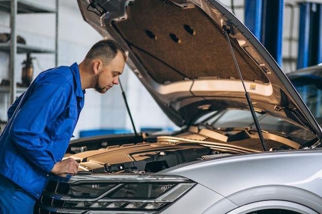 Automonteur die motor van een auto controleert