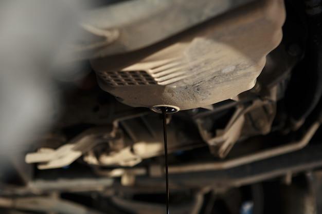 Automonteur die verse olie vervangt en in de motor giet bij onderhoudsreparatieservicestation