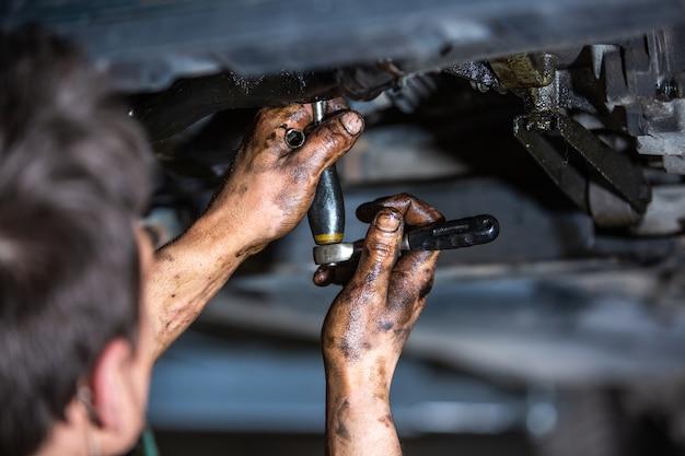 Automonteur doet reparatie, onderhoud olieverversing aan de auto op de hydraulische autolift, autoservice