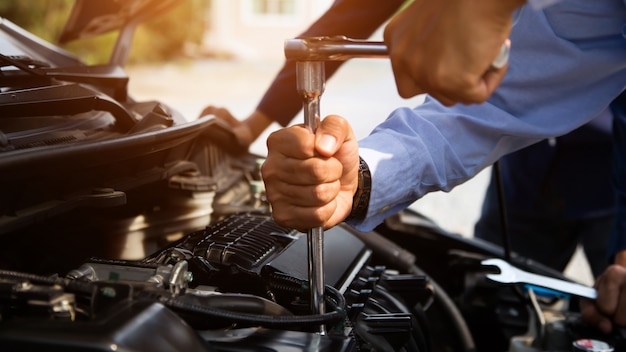 Automonteur handen met behulp van moersleutel om een auto-motor te repareren.