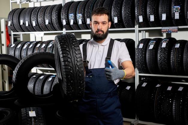 Automonteur in een werkplaats op een stapel banden op zijn werkplek, jonge man in uniform band in handen houden