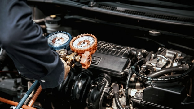 Automonteur met behulp van meetapparatuur voor het vullen van auto-airconditioners.