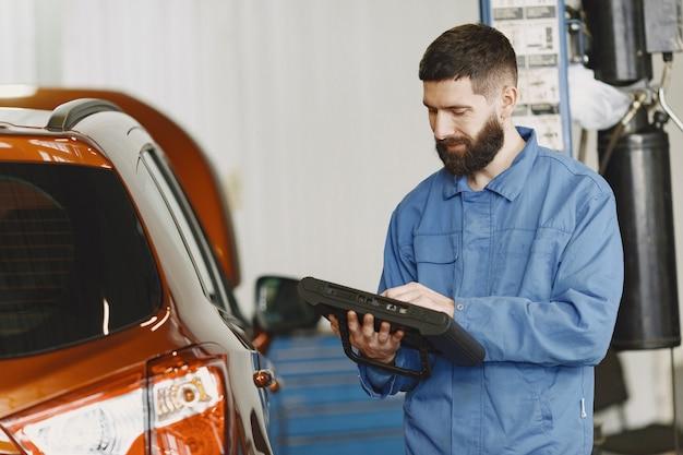 Automonteur met een tablet in de buurt van auto in werkkleding
