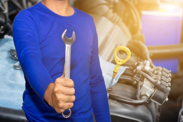 Automonteur met gereedschapscontrole en repareerde een oude automotor bij een tankstation, wissel en repareer voordat u gaat rijden