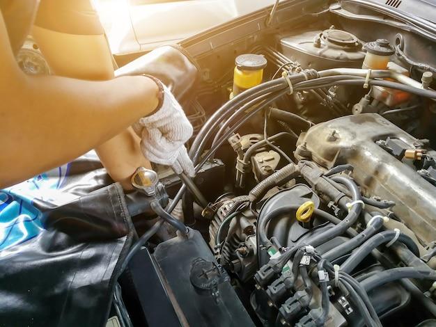Automonteur met gereedschapswerkcontrole en repareerde een oude automotor bij een servicestation, vervang en repareer voordat u gaat rijden