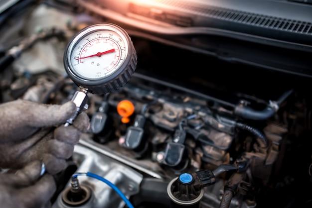 Automonteur staat op het punt de compressie in de cilinder van een automotor te meten met behulp van een diagnostische barometer en gerepareerd in de machinekamer voor een voertuig.