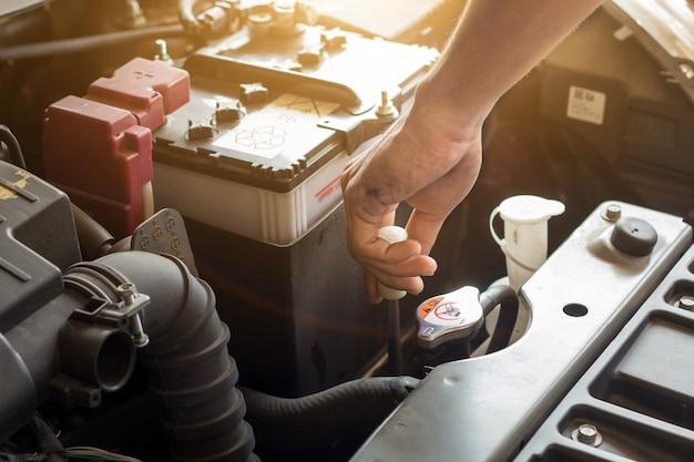 Automonteur werkt systeemwater controleren en een oude automotor vullen bij servicestation, vervangen en repareren voordat u gaat rijden