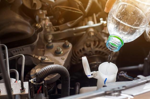 Automonteur werkt systeemwater controleren en een oude motor van een auto bij tankstation vullen, vervangen en repareren voordat u gaat rijden