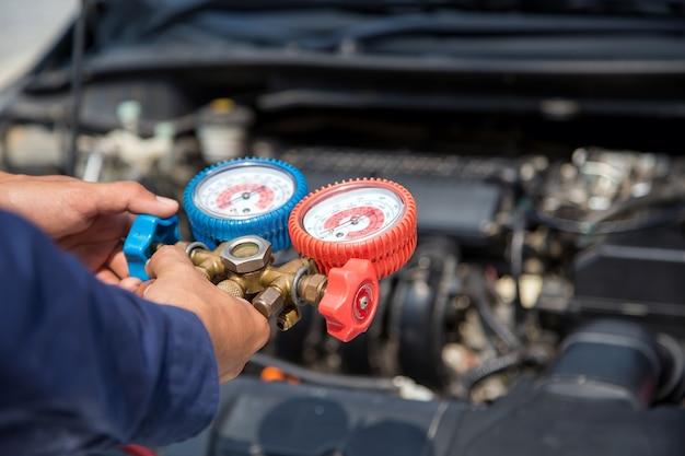 Automonteurs gebruiken meetapparatuur voor het vullen van auto-airconditioners