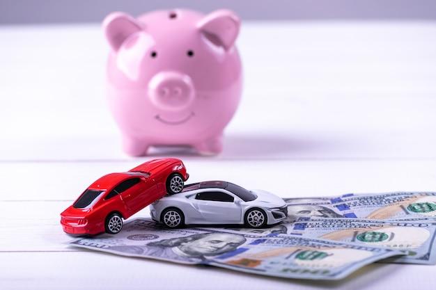 Autoneerstortingongeval op dollarsbankbiljet met spaarvarken. verzekering concept.