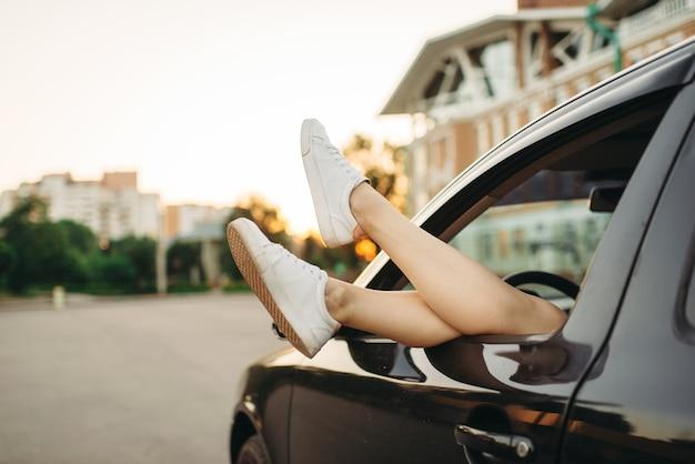 Autopech, vrouwelijke benen steken uit het raam