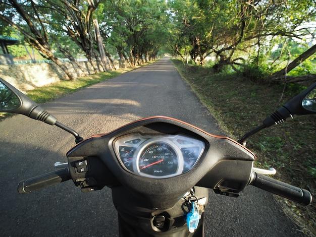 Autoped rijden bij zonsopganglicht op lege landelijke asfaltweg. pov.