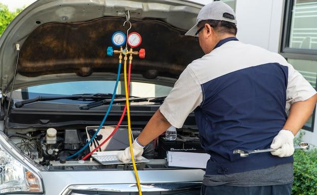 Autoreparateur controleert de motor en het koelsysteem voordat hij op lange vakantie gaat. concept van autoverzorging en onderhoud door experts