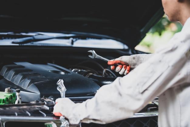 Autoreparateur die een witte uniform draagt en een moersleutel vasthoudt die een essentieel hulpmiddel is voor een monteur