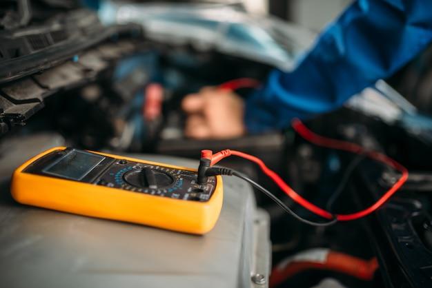 Autoreparateur met multimeter, batterijinspectie. auto-service, diagnose van voertuigbedrading, beroep van elektricien
