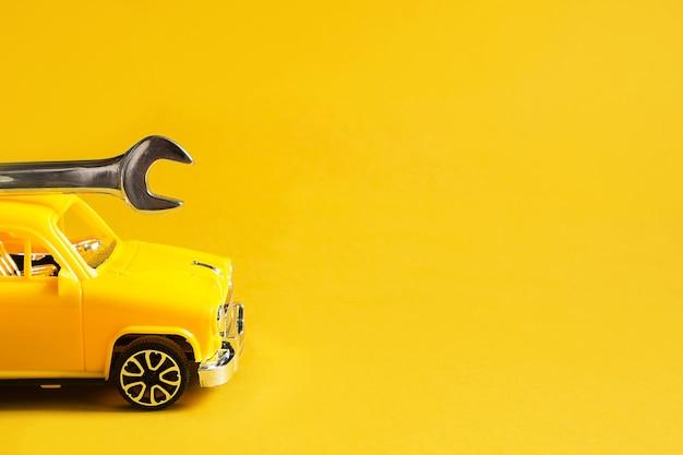 Autoreparatie en reparatie van apparatuur en auto's, dringend vertrek van de kapitein om breuk, loodgieterswerk, constructie te elimineren. reparatieservice auto met verstelbare universele sleutel op gele achtergrond.
