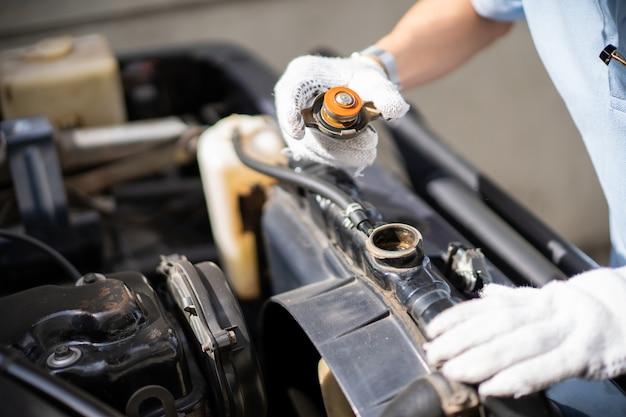Autoreparatiemens die het koelmiddelsysteem, keteltank, in de oude auto controleren.