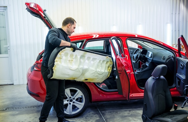 Autoservicemedewerker demonteer het interieur van de auto