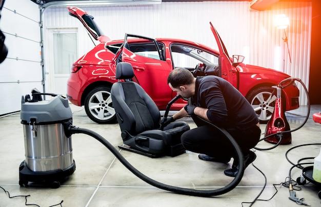 Autoservicemedewerker die autostoeltje schoonmaakt met stofzuiger