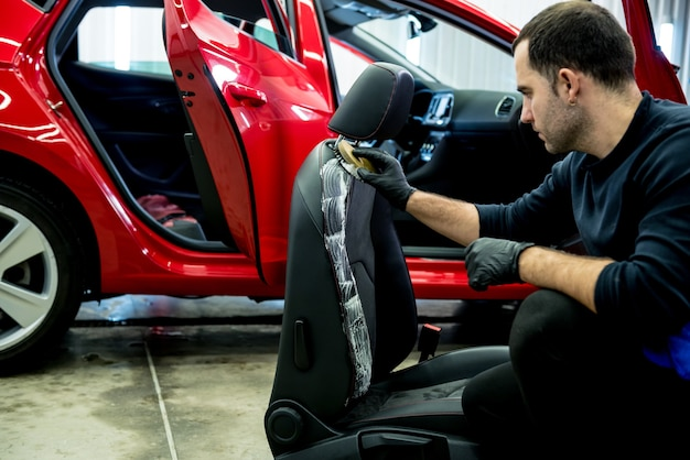Autoservicemedewerker maakt een autostoeltje schoon met een speciale borstel