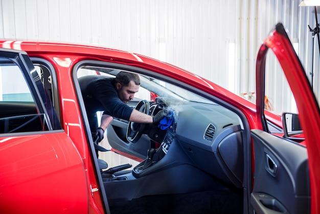 Autoservicemedewerker maakt interieur schoon met stoomreiniger