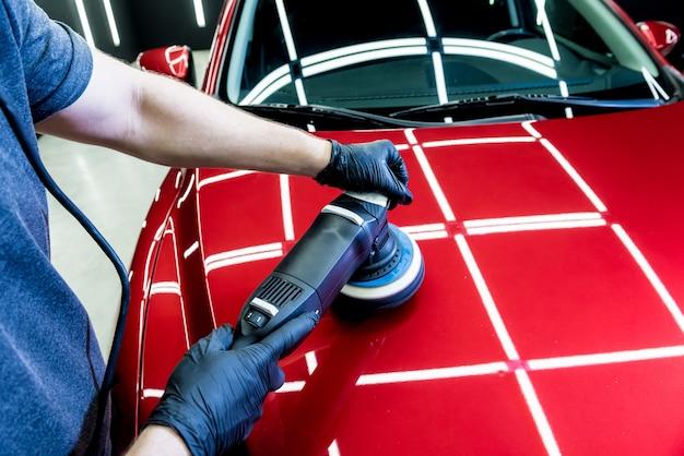 Autoservicemedewerker poetst de details van een auto met een excentrische polijstmachine.